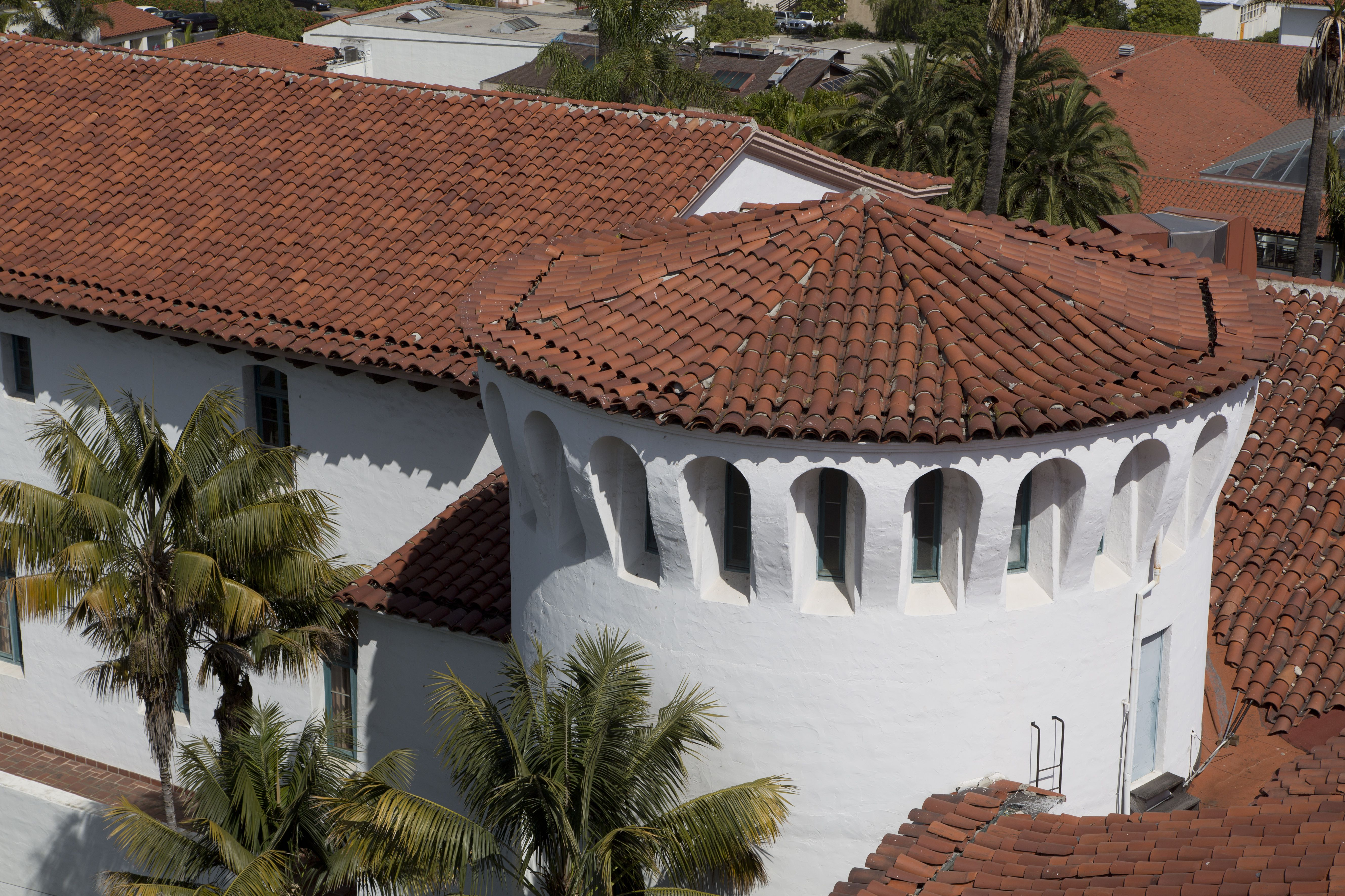 aerial view of red tile roof, gable and circular, on top of a stucco white building with arched windows