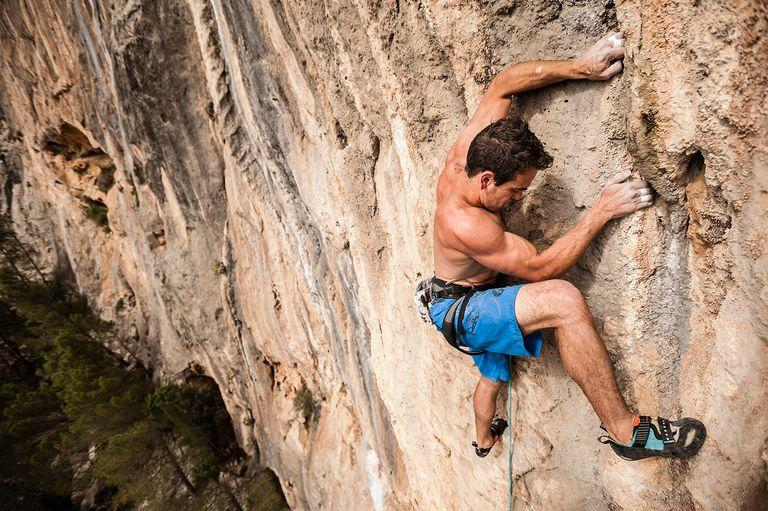 Shirtless mountain-climber climbing