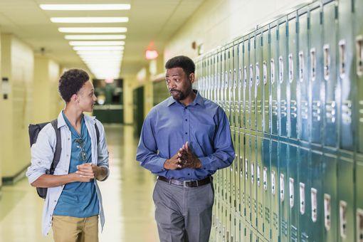 Teacher and high school student walking in hallway