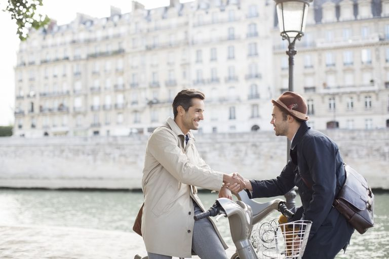 Businessmen handshaking on bicycles along Seine River, Paris, France