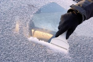 Gloved hand scraping an icy windshield.