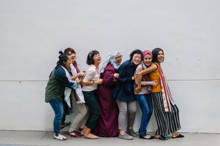 Diverse group of women in a line laughing together against a plain wall.