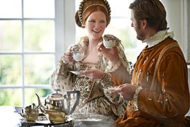A king and queen taking tea together at home