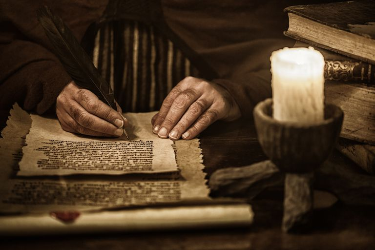 Man writing on parchment with a quill pen by candlelight, sepia photograph.