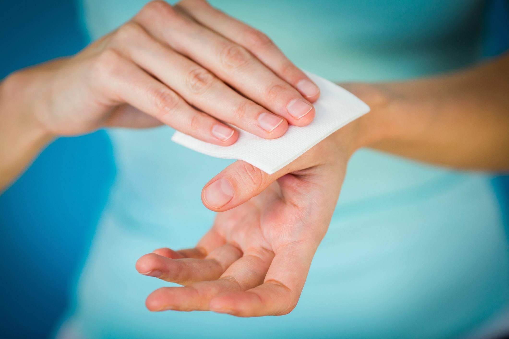 Woman applying cotton pad to hand