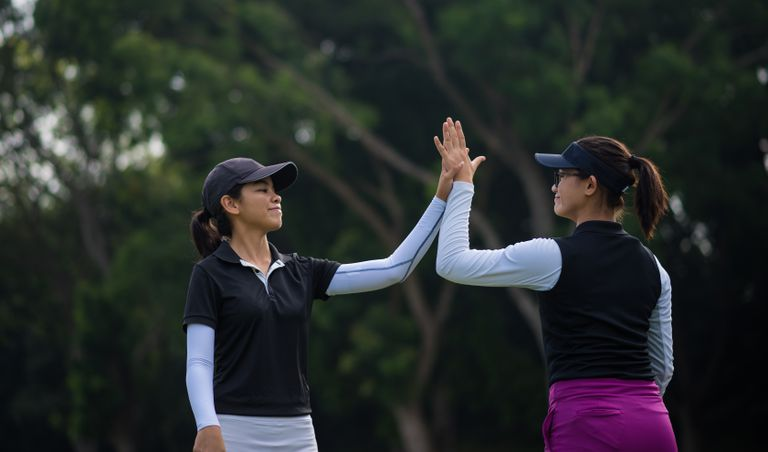 Two golfers, part of a team competition, celebrate a good putt.