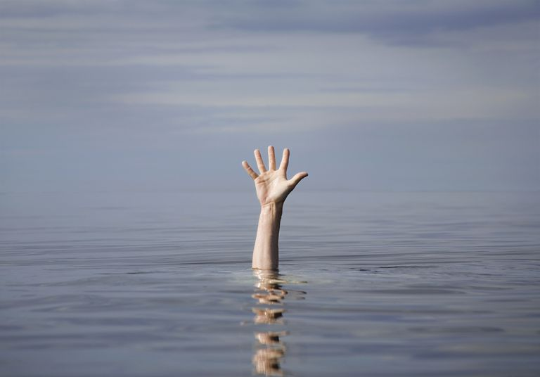 A hand reaches up from underwater, which is a signal for drowning