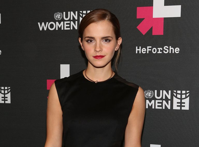 Emma Watson posing in front of UN Women's 'HeForShe' sign.