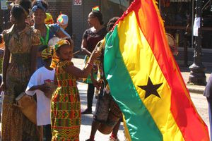 Young girl holding the flag of Ghana in a crowd of people on a sunny day.