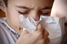 Young boy sneezing into a tissue close up.