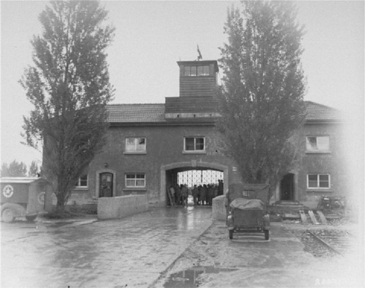 Survivors and U.S. troops at the entrance to the Dachau Concentration Camp.