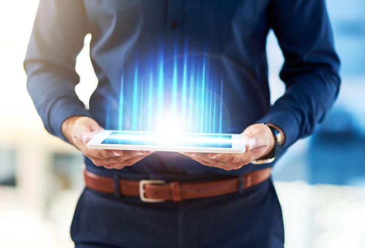 man holding beaming tablet
