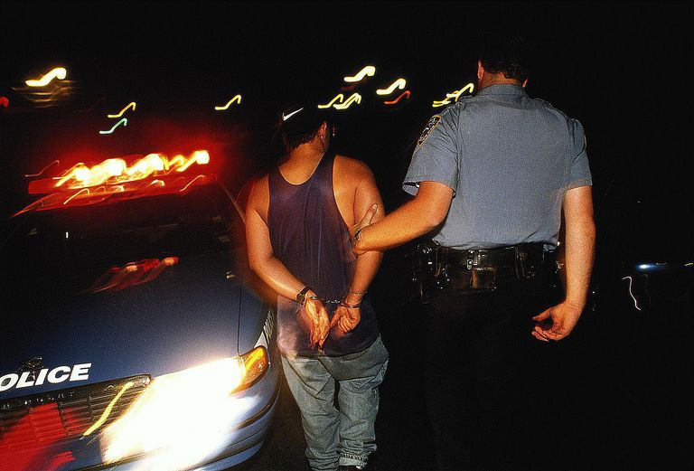 Police officer leading handcuffed man to police car at night