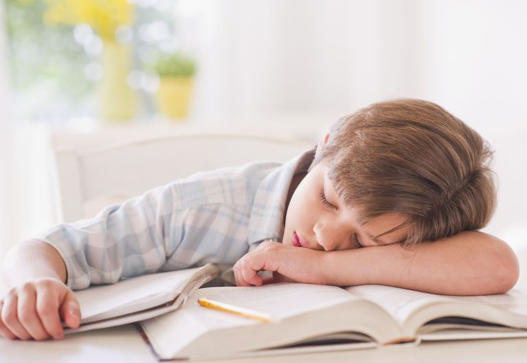 Tired boy sleeping on books