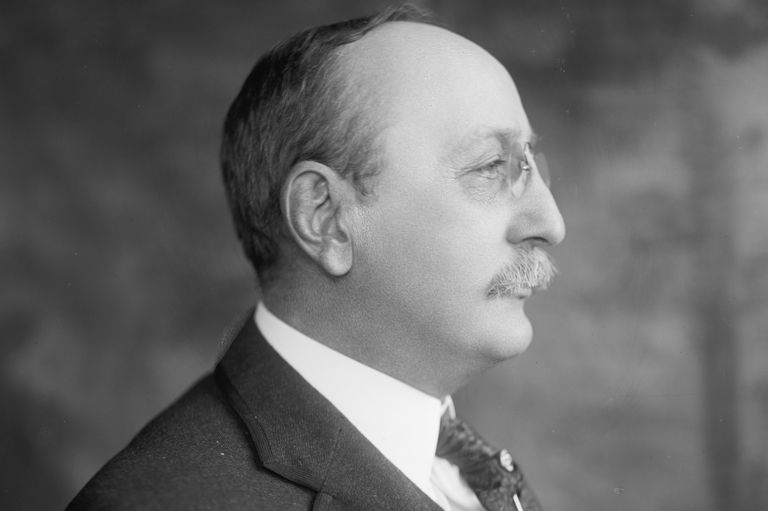Black and white head and shoulder profile of Cass Gilbert, mustache, pince-nez glasses, three-piece suit