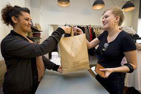 Vendor handing bag across counter to customer