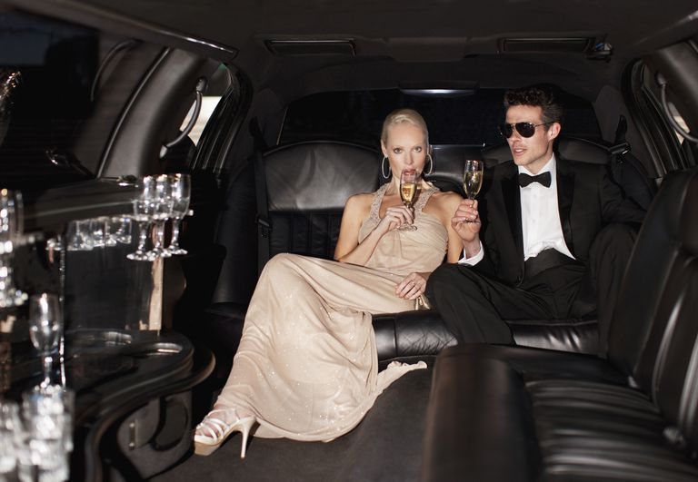 Formally dressed caucasian woman and man sip champagne in limousine