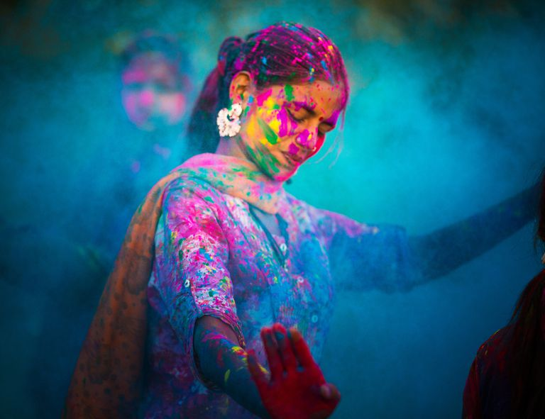 Vivid color photograph of an Indian woman dancing, covered in paint against a blue background.