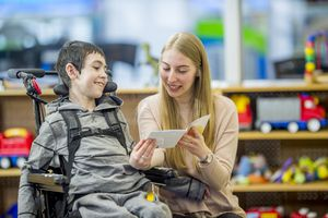 Young woman teacher reading a story to a boy in a wheelchair