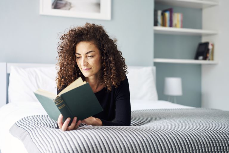 Mixed Race Woman engrossed reading a book at home on the bed in the daytime