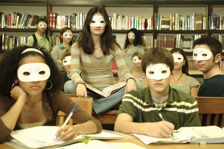 A group of High School students in a library all wearing masks