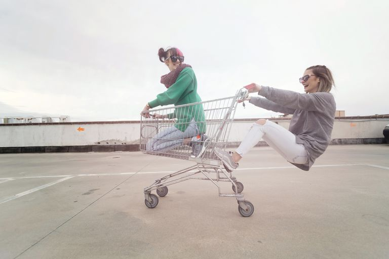 Two young women playing with empty shopping cart