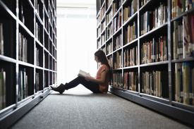 Woman sitting om floor in library between the stacks reading a book