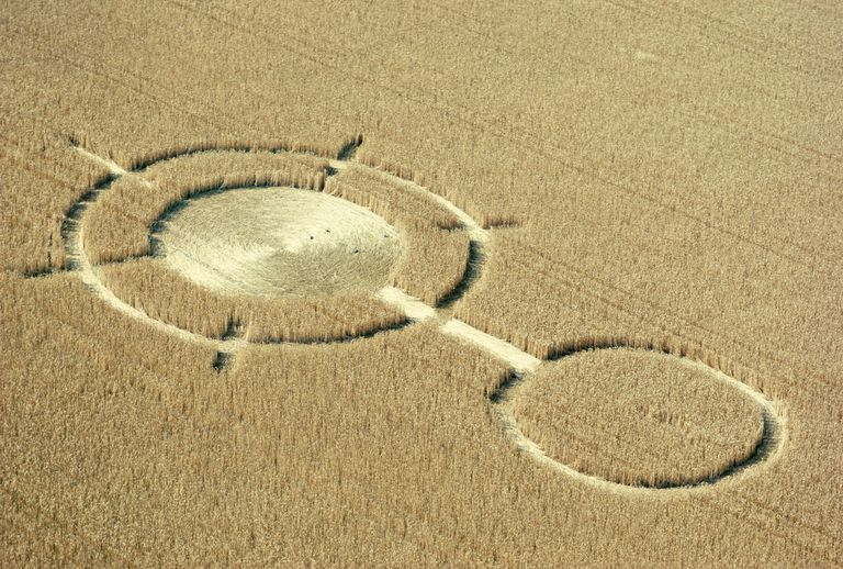 An intricate crop circle in a large field as seen from above.