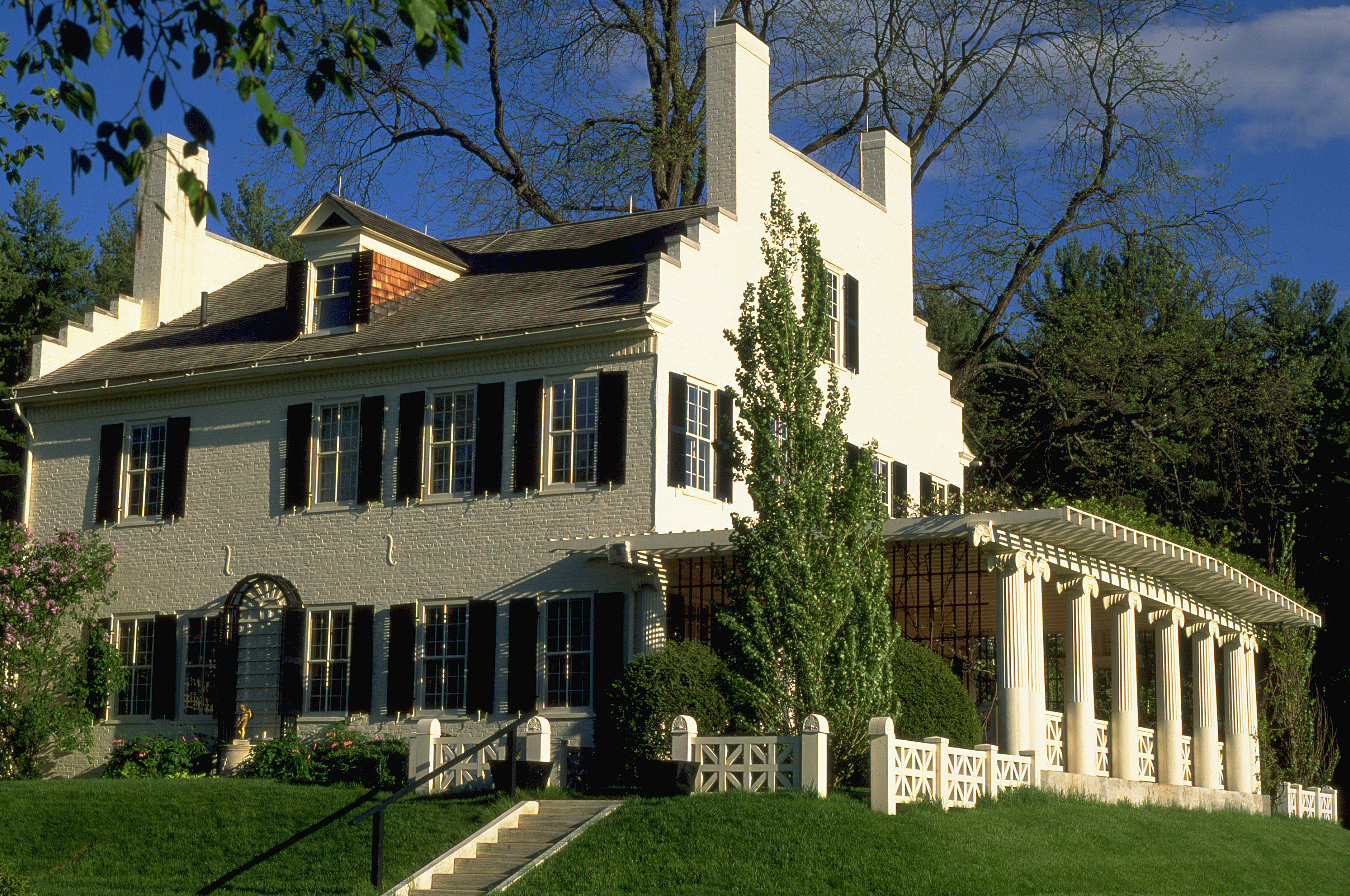 large two-story white house with dark shutters, collonade side porch, and large parapets on each side gable