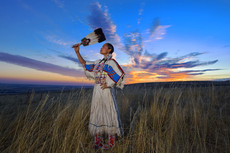 Native American woman in traditional dress standing among grass on prairie