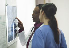 Female black doctor and nurse discussing x-rays