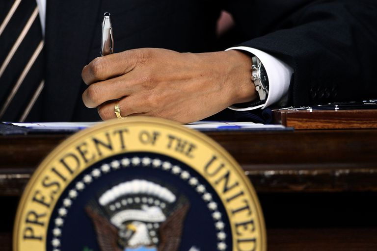 President Obama's signs the STOCK Act into law on the Resolute Desk in the Oval Office