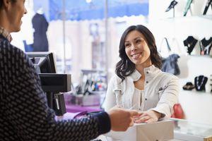Man handing clerk credit card in clothing store