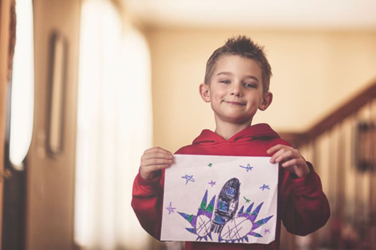 boy holding his drawing of a rocket flying into space.