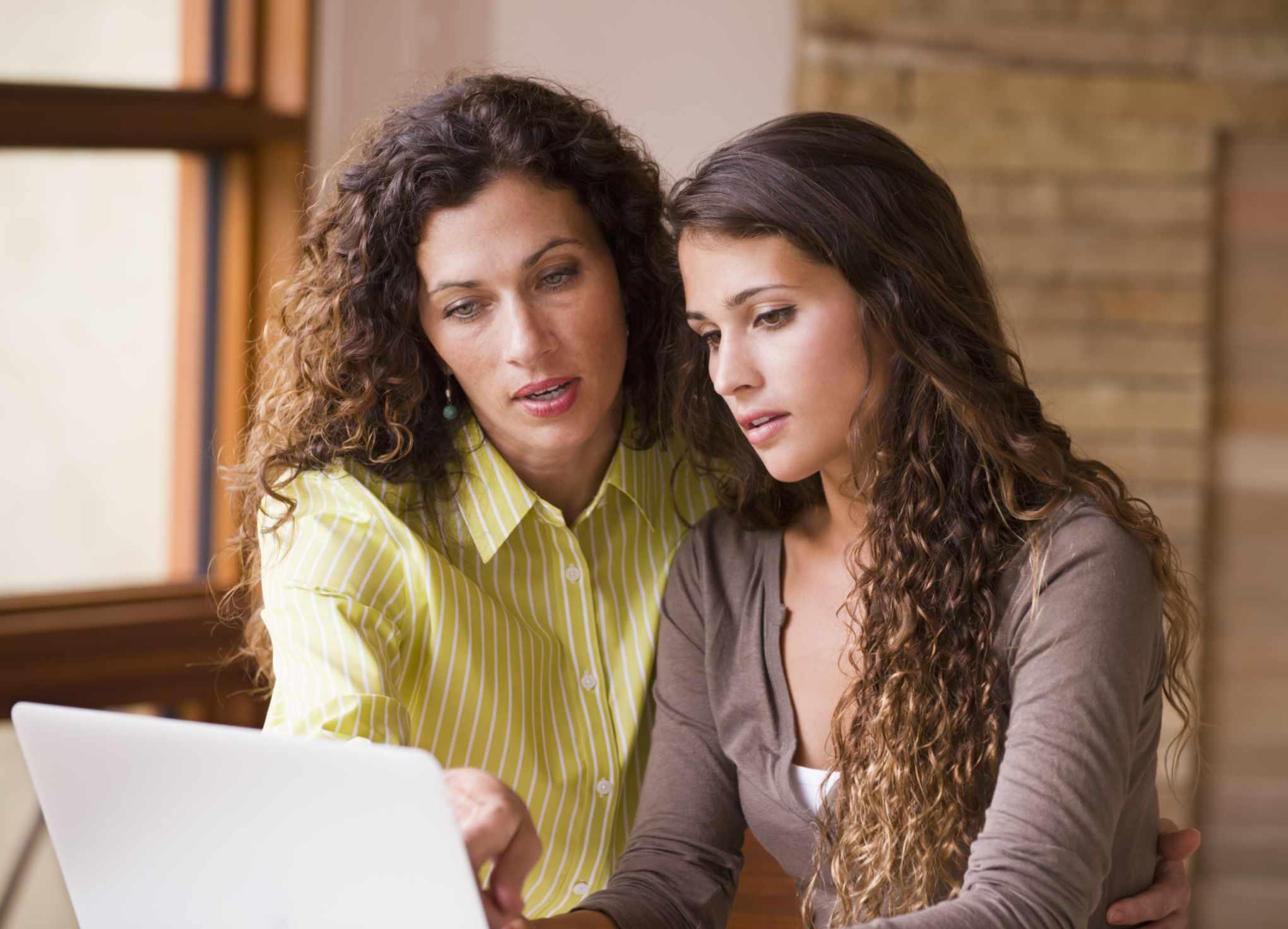 Dos mujeres llenando planilla en computadora