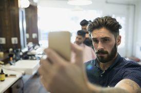 Bearded man taking selfie in barber shop