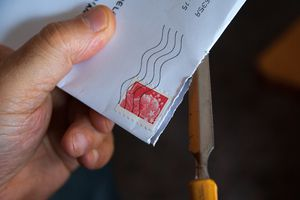 Close up of a person opening a letter.