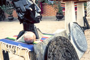 Handmade obsidian aztec head statue on sale amongst other mesoamerican artifacts.