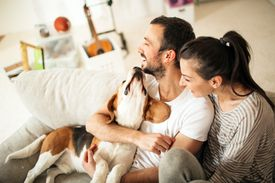 Couple on couch with dog.