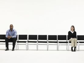 A black man and a white woman sitting apart symbolize the concept of social distance.