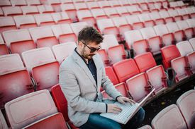 Man works on a laptop in a stadium