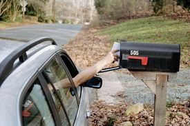 Reaching into a mailbox from a car on a road