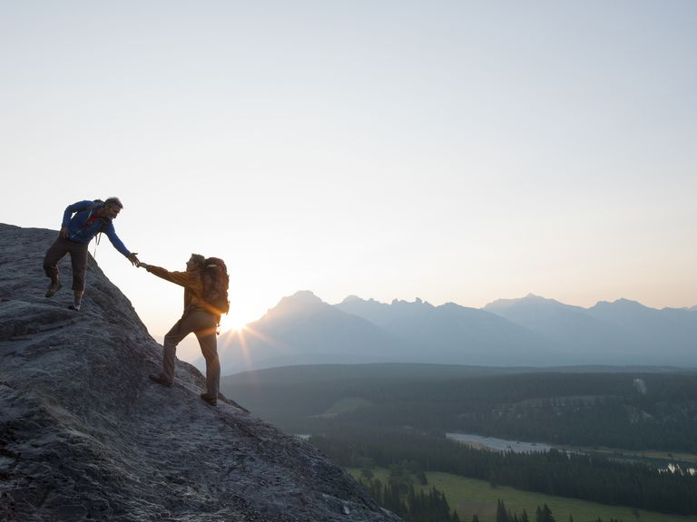two people helping each other on a mountain