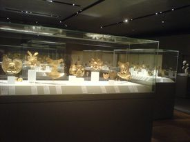 Collection of gold artifacts at a museum.