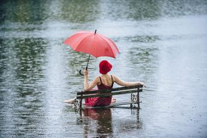Woman sitting on bench in flood