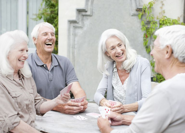 Group of senior citizens sitting together outside playing cards and laughing.