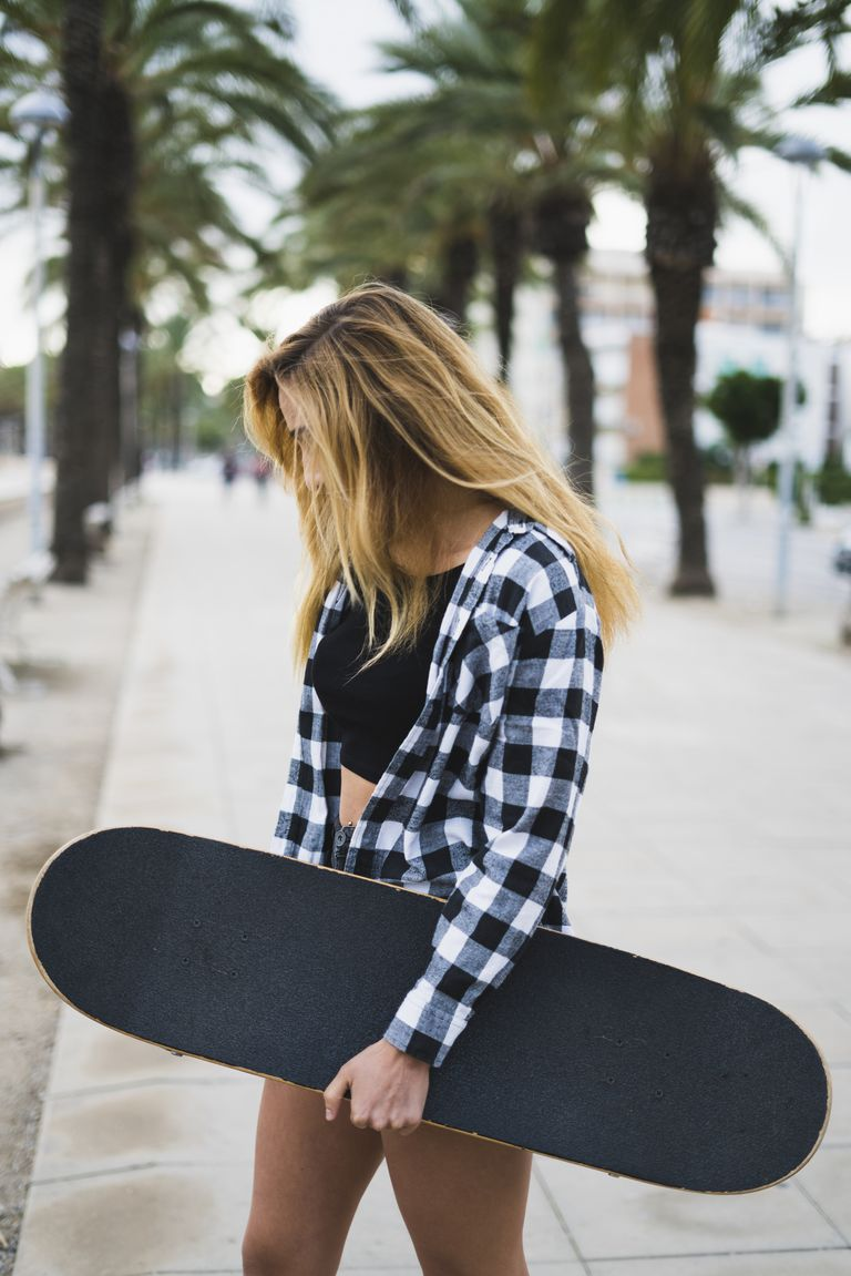 Spain, young woman with skateboard
