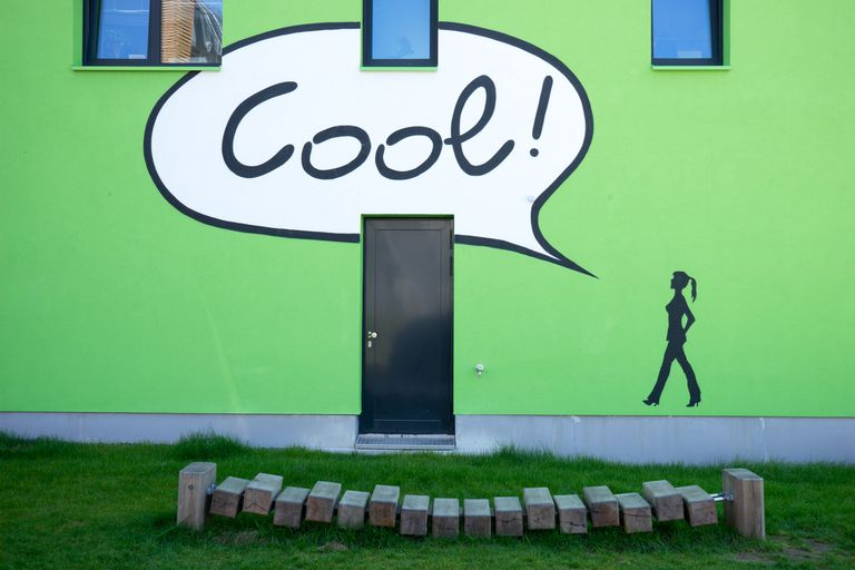 Green Apartment Building With Painted Figure Voice Balloon That Says Cool