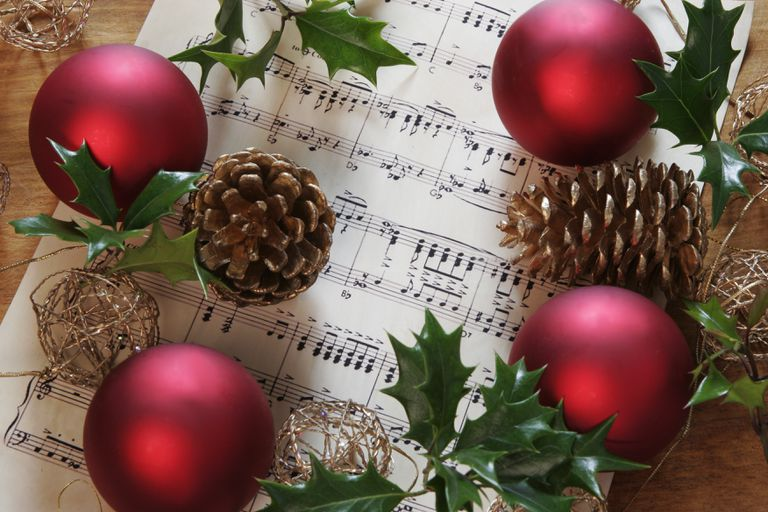 christmas scene with holly fir cones and sheet music