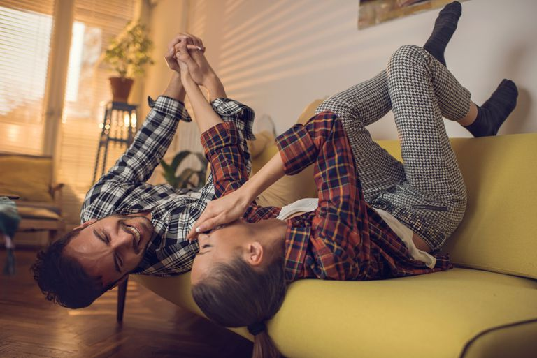 Cheerful couple having fun in the living room and laughing.